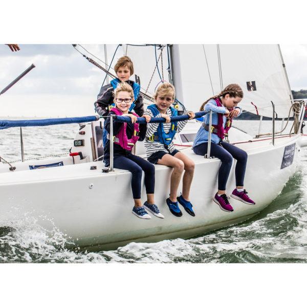 4 children in Spinlock Deckvest Cento Junior Lifejacket on white sailing boat