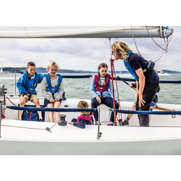 children and man in Spinlock Deckvest Cento Junior Lifejacket on white boat